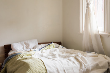 Unmade futon style bed with wooden bedhead with rumpled sheets, pillows and blankets in corner of room with white curtain on window