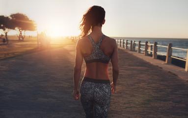 Fitness woman walking on a seaside promenade at sunset.