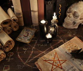 Magic book with pentagram, the tarot cards and candles on wooden planks
