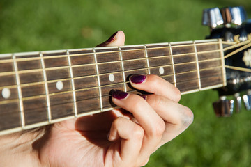 Girl playing guitar in the park in summer. The image is a close-up of hands making chords on the guitar neck.