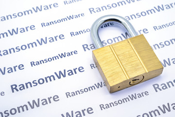 Brass master key on white paper of seamless pattern with Ransomware word