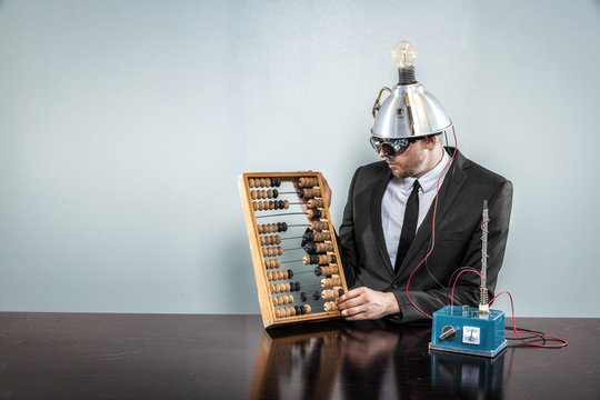 Businessman sitting at office desk with abacus