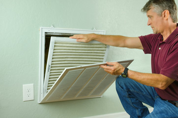 Professional repair service man or diy home owner removing a dirty air filter on a house air conditioner so he can replace it with a new clean one.