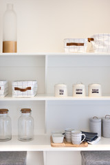 Natural kitchenware in the shelf including glass bottles and mug