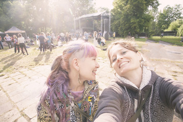 Two girls taking selfie in front of the stage on music open air summer festival