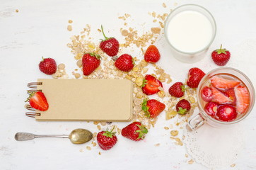 Blank notebook with craft brown pages, ripe strawberries and oat muesli for breakfast
