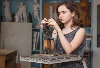 Teen Girl molds from clay sculpture in the artist's studio.