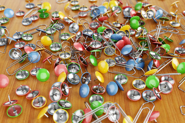 Office colored paper clips and drawing pins scattered on a table