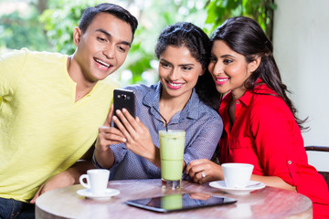 Indian girl showing pictures on phone to friends