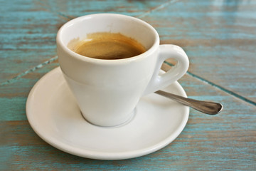 Photo of white cup of coffee on teal blue table