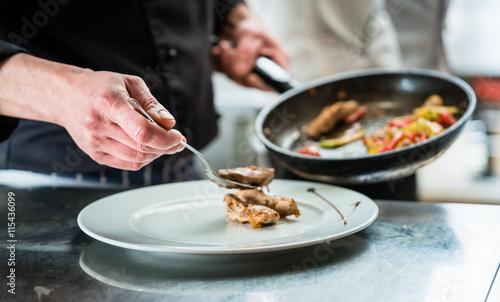 Koch beim anrichten  Koch oder Küchenchef beim Anrichten von Essen, ein Gericht mit ...