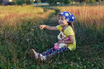 Девочка с игрушкой сидит в траве и