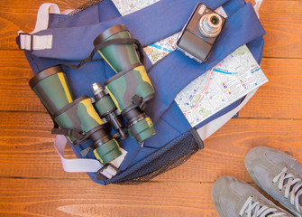 The preparation for the trip, travel, backpack, binoculars, camera, map on wooden background