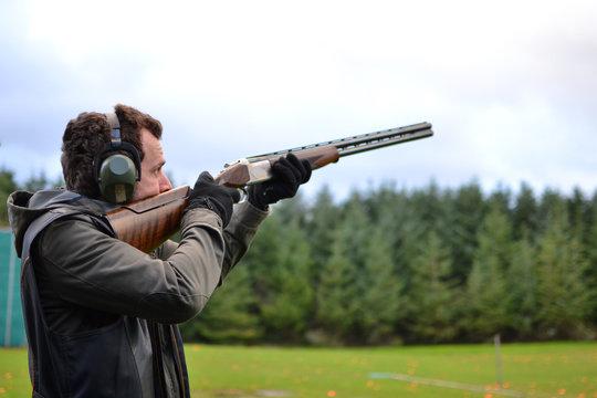 man shooting shotguns at clay pigeon outdoors