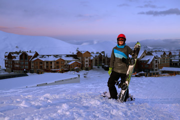 Pretty Girl snowboarder stands on front of hotel ski resort