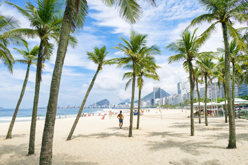 Scenic view of Copacabana Beach through palm trees from the Leme neighborhood in Rio de Janeiro, Brazil