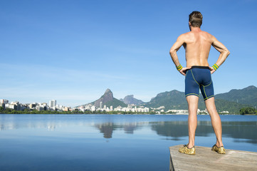 Shirtless athlete in blue compression shorts standing in front of the Rio de Janeiro, Brazil skyline at Lagoa Rodrigo de Freitas lagoon