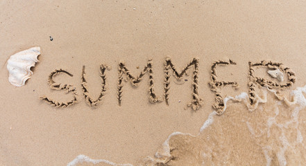 summer text background written on sand and piece of sea.