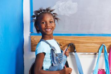 Afrikanisches Mädchen an Garderobe im Kindergarten