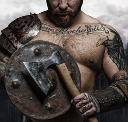 Cropped tattooed male's body with vikings shield.