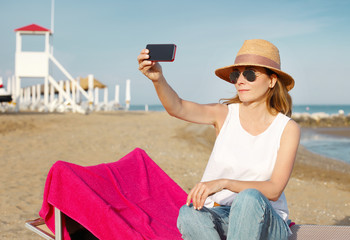Relaxing on the beach. Middle age woman taking a selfie with mobile phone at seaside.