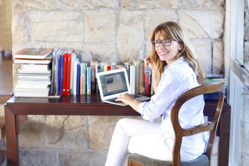 Shot of a successful mature woman with mobile and laptop sitting at desk and working online at home.