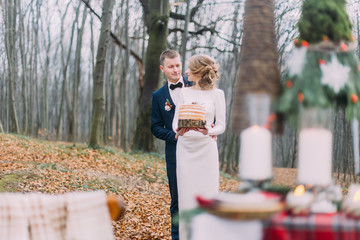 Happy young wedding couple walking and hugging near the decorated table for Christmas holidays in autumn forest.