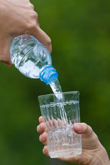 hand pouring water from bottle into glass on the green backgroun
