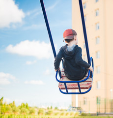 boy on swing riding high