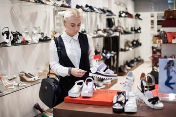 Woman choosing footwear in the mall.