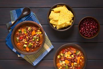 Veganischer Chili aus Kidneybohne, Karotte, Zucchini, Paprika, Mais, Tomate, Zwiebel und Knoblauch, mit Maischips und rohe Bohnen an der Seite, fotografiert mit natürlichem Licht