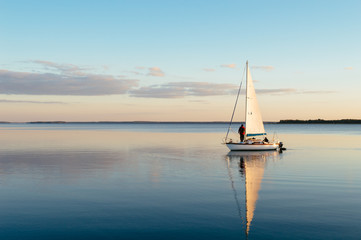 Sailing boat on a calm lake with reflection
