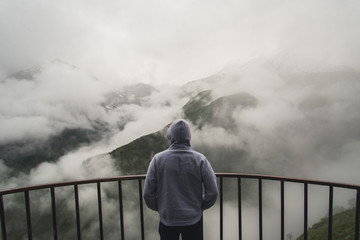 View from behind of a man standing at view point looking to beautiful landscape with foggy mountains in the distance Wall mural