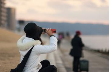 宍道湖畔でスマートフォンのカメラで撮影する女性