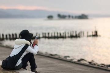 宍道湖畔でスマートフォンを操作する女性