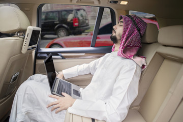 Arabian man with laptop resting in car