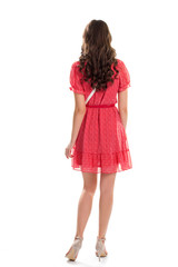 Girl wears red dress. Back view of young woman. Pretty model on white background. What a charming look.