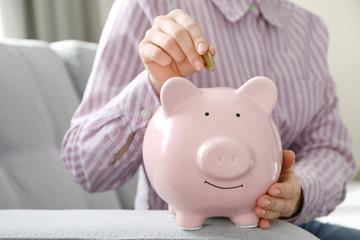 Female hand putting money into piggy bank indoors