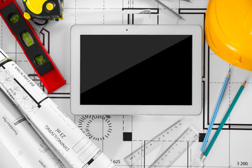 Construction blueprints with tools and tablet, top view