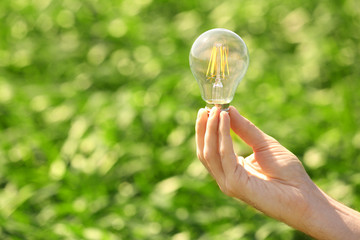 Female hand holding light bulb on the green grass background