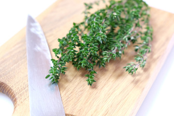 High key image of organic thyme fresh herb on a wooden chopping board with a knife blade. Very shallow depth of field.