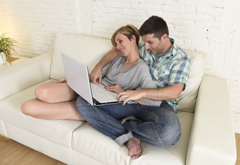 beautiful couple in love on couch together with laptop computer happy at home using internet