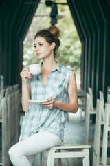 Woman enjoying a large cup of freshly brewed hot tea or coffee in the morning at restaurant