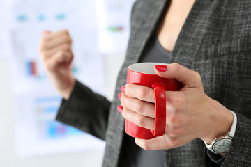 Female hands hold red mug of hot coffee