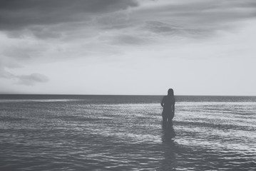 Silhouette of young woman walking on sea at sunset