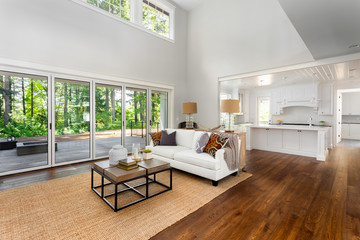 Large living room interior and kitchen in new luxury home. Vaulted Ceilings and bank of windows and sliding glass lead out to deck and lush forested backyard