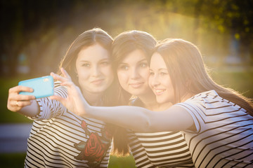 Three similar to each other sisters girls taking selfie. Group o