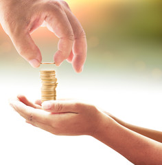 Investment concept: Hand of father give one coin into stacks of golden coins in hands of son over blurred nature background.