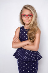 Portrait of a lovely little girl daughter in long blond hair and violet dress with white dots and red glasses with white dots looks at the camera, photo on the white background amazing eyes
