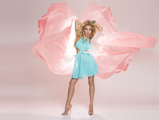 Beautiful young sexy blond woman standing in a rainbow dress billowing in the wind billowing gauzy butterfly-shaped